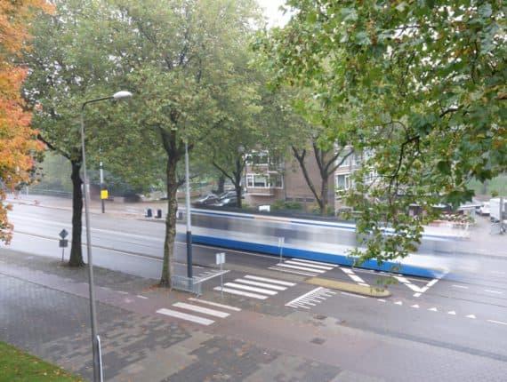 Foto uit de cursus fotografie basis: bewegende tram tussen de bomen van bovenaf gefotografeerd