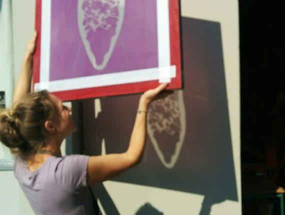Een cursist hangt een werk uit de cursus zeefdrukken aan de muur