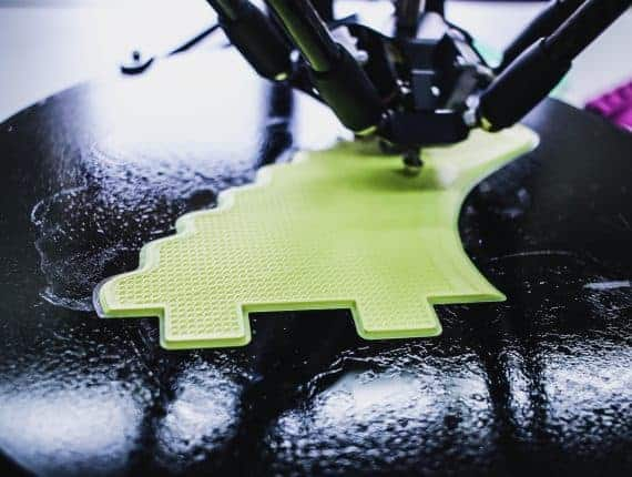 3D printer printing something bright green, it is unclear what it is.