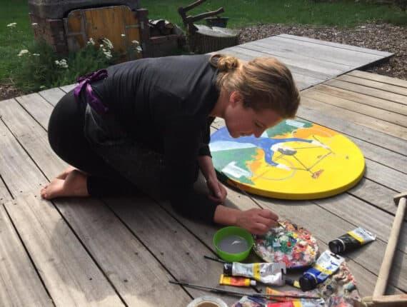 Foto van Natasja van der Jagt schilderend op een houten dek, buiten.