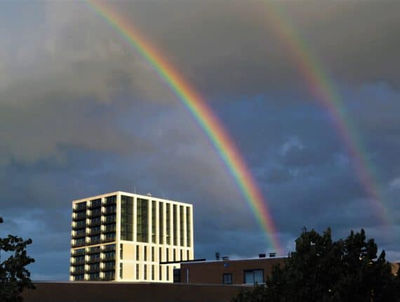 Tekens van Hoop, een foto van een regenboog tegen een donkere lucht